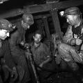 Auf engstem Raum und ohne Tageslicht: Bergarbeiter und ein Steiger untertagen in der Grube Göttelborn im Saarland (1955).