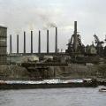 Industriestandort Nordrhein-Westfalen: Vor der Fabrikanlage der Niederrheinischen Hütte AG bei Duisburg fährt ein Schiff auf dem Weg nach Holland mit fabrikneuen Autos von Ford aus Köln vorbei (1963).